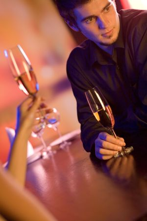 Young couple with champagne glasses in restaurant, celebrating or on romantic date photo