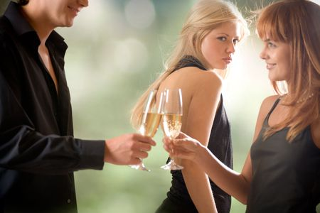 jealousy: Young couple holding glasses with champagne and woman looking at them, outdoors, focus on woman with blond hair