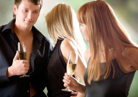 flirt: Young couple and women holding glasses with champagne, outdoors, focus on woman with blond hair and man