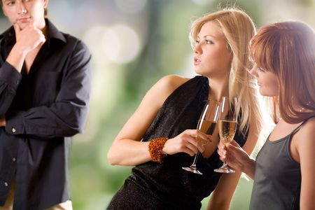 them:  Two women holding glasses with champagne and young man looking at them, outdoors, focus on women
