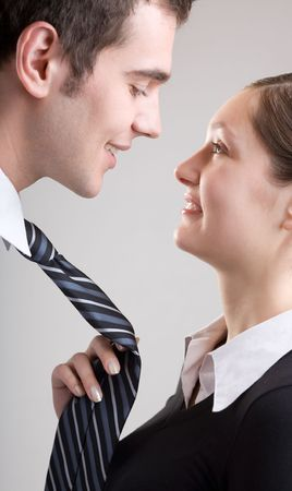 to tempt: Young woman holding mans tie, funny Stock Photo