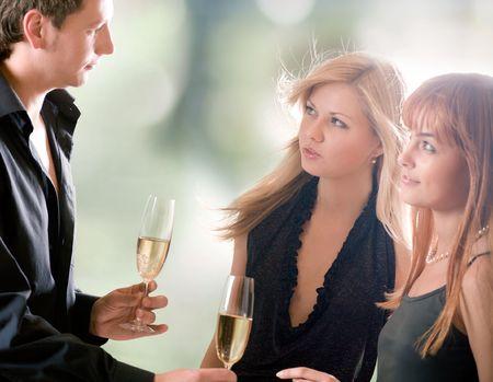 coquetear: Joven con dos vasos de champ�n y dos mujeres de pie juntos, al aire libre, se centran en la mujer con el cabello rubio y el hombre  Foto de archivo