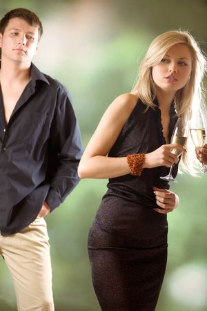 Two women holding glasses with champagne, young man looking at them, outdoors; focus on blond woman Stock Photo - 844497