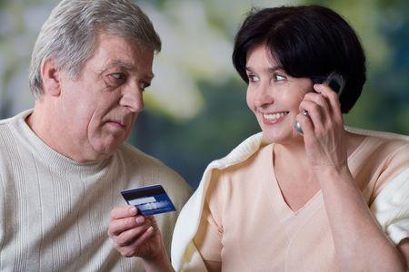 pareja madura feliz: Pares maduros felices que hacen la verificaci�n de la tarjeta o que hacen compras en tienda del Internet por la tarjeta de cr�dito