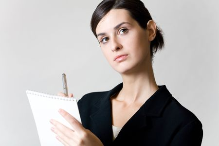 Young secretary or businesswoman with pen and spiral note-book photo