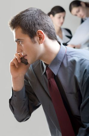 Businessman with cellphone and two businesswomen on background, out of focus Stock Photo - 846014