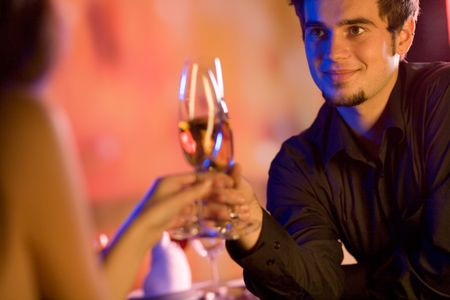 suprise: Young couple sharing champagne glasses in restaurant, celebrating or on romantic date. Focus on man.