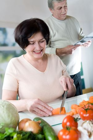 Elderly happy couple cooking at kitchen. Focus on woman.  photo
