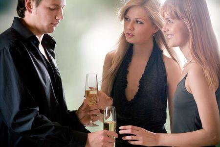 gelosia: Giovane uomo con due bicchieri di champagne e due donne in piedi insieme, all'aperto