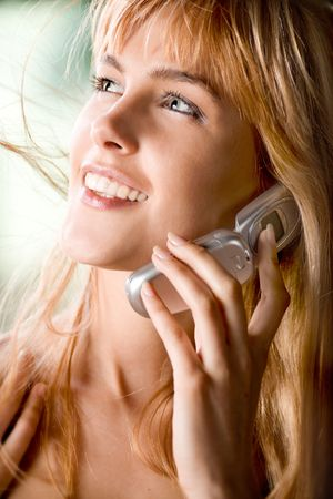 Young redhaired woman smiling and keeping mobile phone, outdoors photo