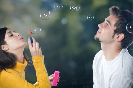 love blow: Young couple blowing bubbles, outdoors  Stock Photo