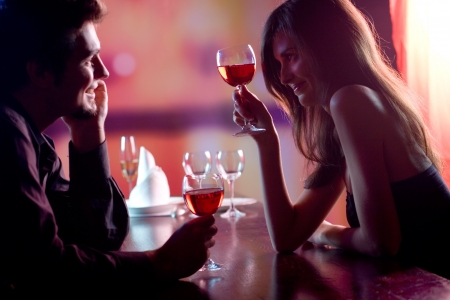 Young couple sharing a glass of red wine in restaurant, celebrating or on romantic date. Focus on woman with glass. photo