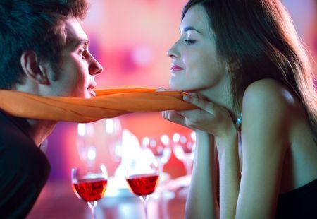 coquetear: Atractiva joven pareja feliz en el restaurante, celebrando o por cita rom�ntica