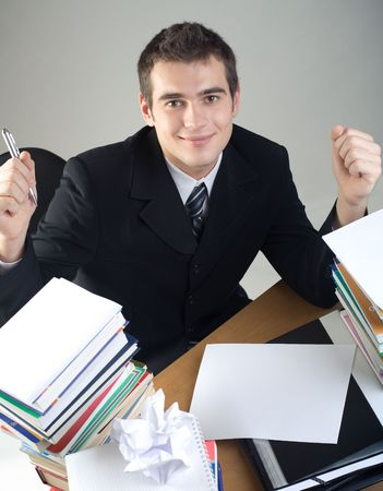 Young student or businessman sitting at the table with pen and blank paper, smiling photo