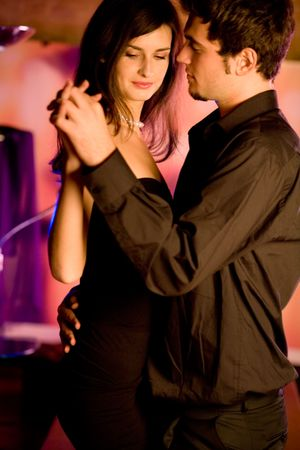 lovers embracing: Young couple dancing at the restaurant or cafe Stock Photo