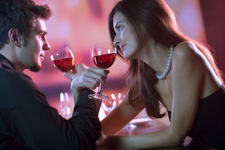 Young couple sharing a glass of red wine in restaurant, celebrating or on romantic date Stock Photo - 872920