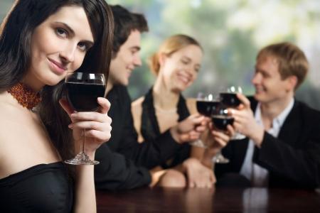 jovenes tomando alcohol: Dos parejas j�venes con gafas de color rojo-vino en la celebraci�n o parte