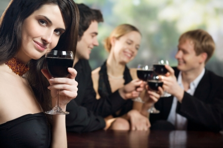 horizontal bar: Two young couples with red-wine glasses at celebration or party