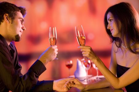 suprise: Young couple sharing champagne glasses in restaurant, celebrating or on romantic date