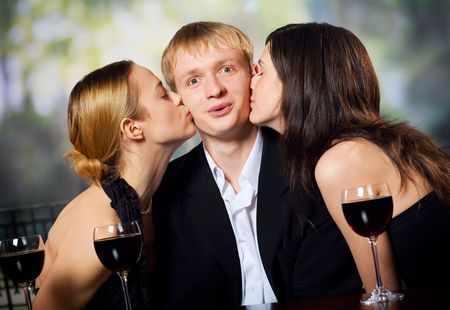 Two young attractive sweet women kissing man with redwine glasses at the celebration or party  photo