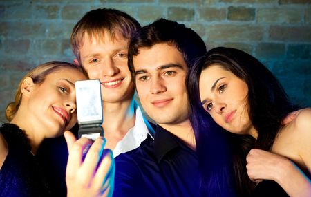 Young embracing smiling people taking photograph by cellphone and posing at celebration or night party Stock Photo - 872939