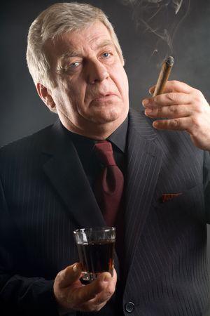 hombre fumando puro: Hombre de negocios mayor con la bebida y el cigarro, fumando Foto de archivo