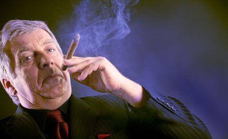 man smoking: Elderly business man smoking a cigar in night club