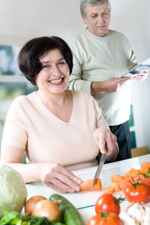 Elderly happy couple cooking at kitchen photo