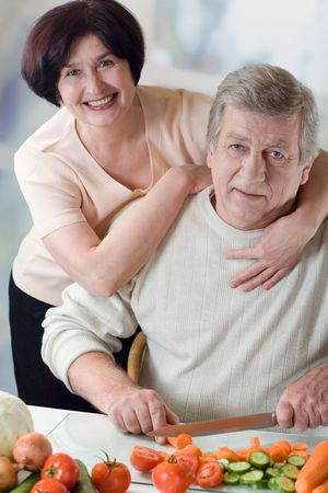 Elderly happy couple cooking at kitchen, embracing Stock Photo - 883229