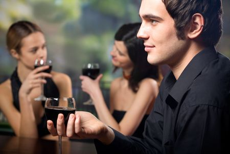 Young handsome man with glass of red-wine and two attractive women at celebration or party photo