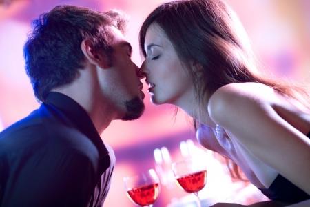 novios besandose: Joven pareja besarse en un restaurante, celebrando o en la fecha rom�ntica