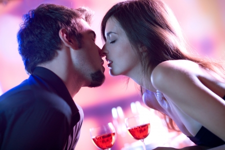 women kissing: Young couple kissing in restaurant, celebrating or on romantic date