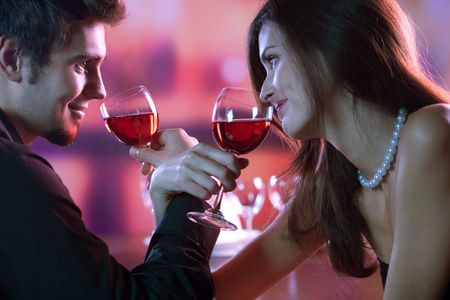 Young couple sharing a glass of red wine in restaurant, celebrating or on romantic date photo