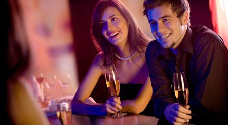 suprise: Young people with champagne glasses in restaurant, meeting