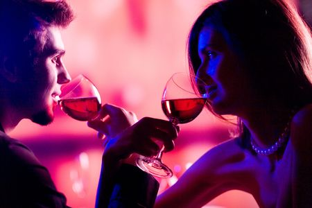 suprise: Young couple sharing a glass of red wine in restaurant, celebrating or on romantic date
