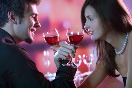 romantico: Pares j�venes que comparten un cristal de vino rojo en restaurante, celebrando o fecha rom�ntica
