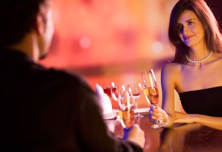 suprise: Young couple sharing champagne glasses in restaurant, celebrating or on romantic date. Focus on woman. Stock Photo