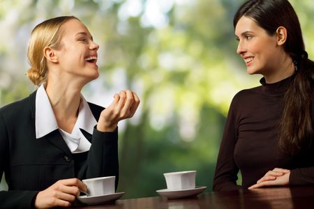 Two smiling attractive young business women chatting on coffe break, outdoor photo