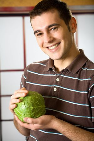 Young attractive happy smiling funny man with cabbage photo