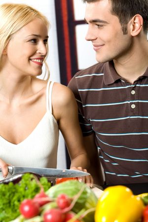 Young attractive happy smiling couple cooking at kitchen photo