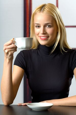 coffeebreak: Young attractive smiling business woman drinking coffee at coffee-break Stock Photo