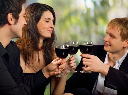 Dos jóvenes feliz sonriendo coquetear con hombres atractivos mujer con rojo-vino, en la celebración o parte