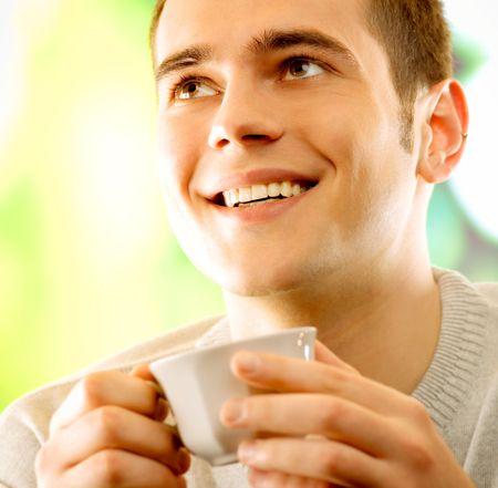 hombre tomando cafe: J�venes sonrientes hombre feliz bebiendo caf�, al aire libre  Foto de archivo
