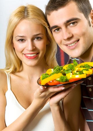 Young attractive happy smiling couple with plate of vegetable salad photo