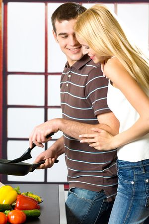 Young attractive happy smiling couple playfully cooking at kitchen photo