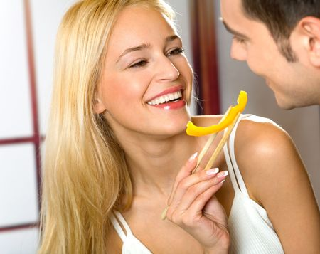 Young attractive happy smiling couple eating playfully vegetables, indoors photo