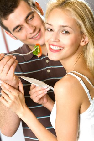 pareja comiendo: Pareja joven atractiva feliz sonriendo juguetonamente comer verduras, en interiores