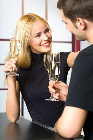Young attractive happy smiling couple celebrating with champagne, indoors photo