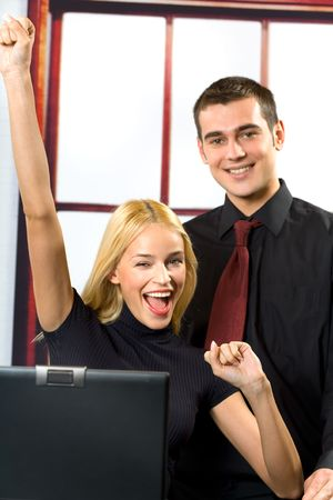 Two young happy smiling successful business people on laptop, working, chatting, playing or searching in internet Stock Photo - 955970
