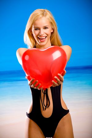 Young attractive woman in swim wear, holding a red heart Stock Photo - 1000819